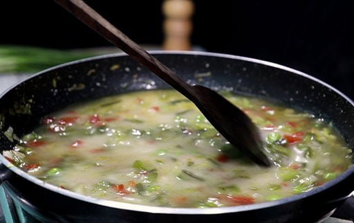 mix-cornstarch-water-mixture-in-vegetable-soup-by-wooden-spatula