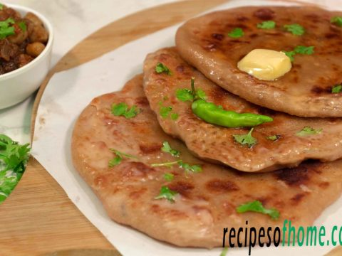 aloo paratha place on wooden food plater topping with butter and gren chili