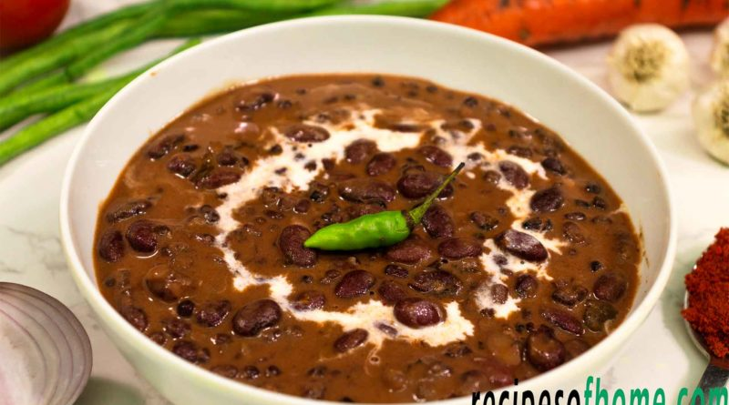dal makhani served in a white bowl garnish with cream and green chili