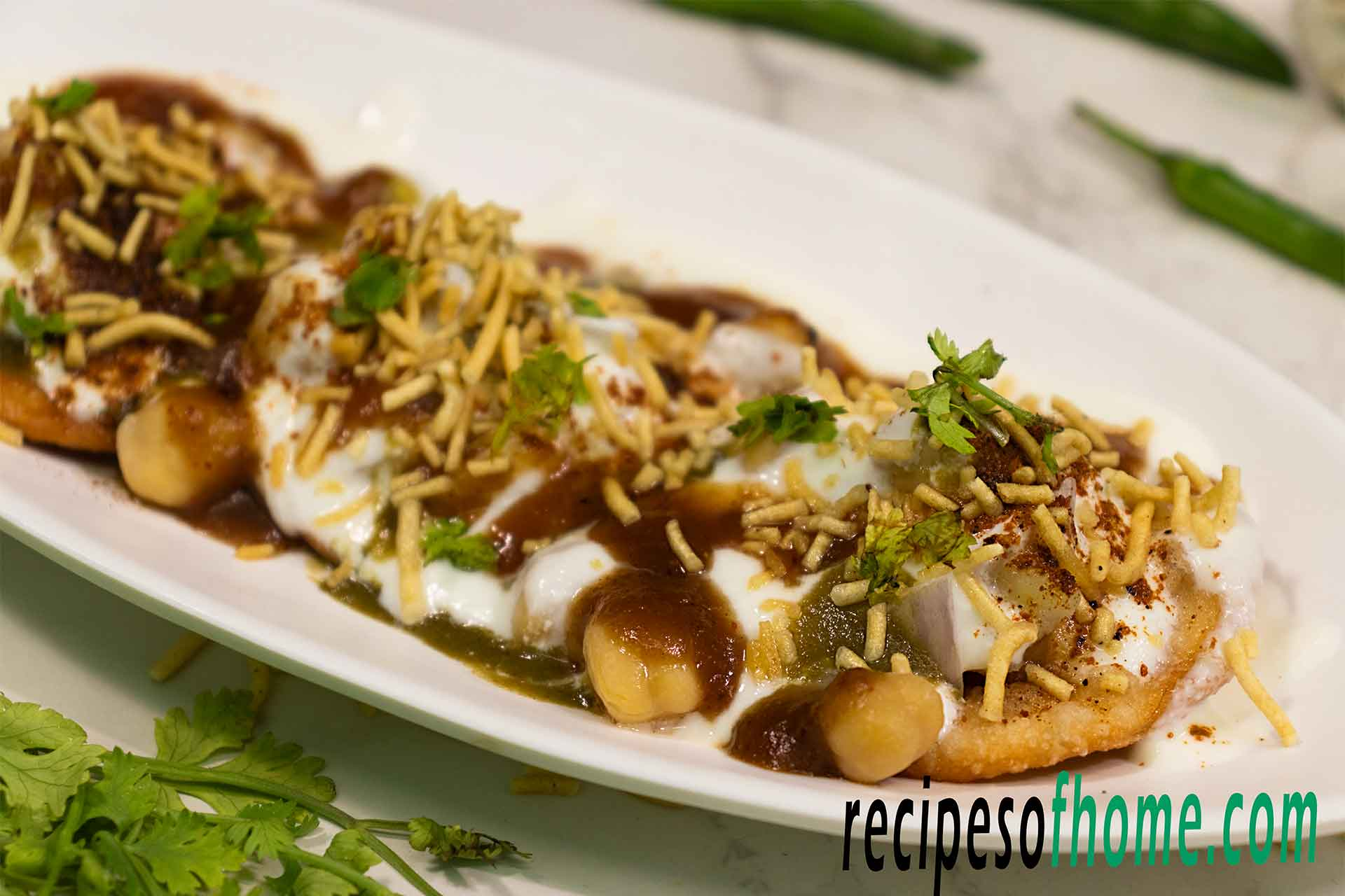 dahi papdi chaat recipe serving on white plate garnish with sev and chopped coriander leaves