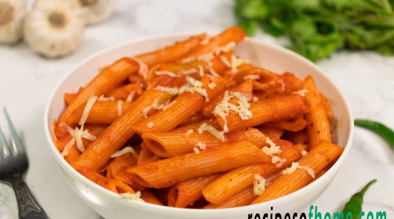 red sauce pasta recipe serve on white bowl garnish with grated cheese from top