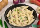 Italian white sauce pasta recipe serve on black bowl garnish with grated chees