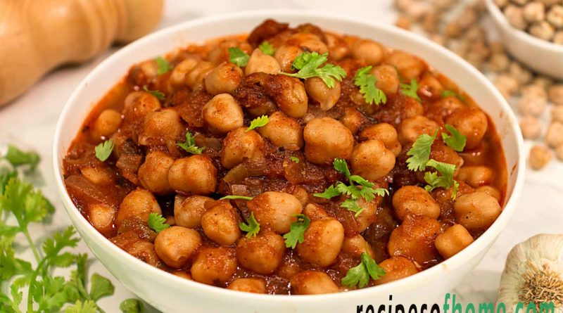 chana masala recipe serve on white bowl garnish with chopped coriander leaves