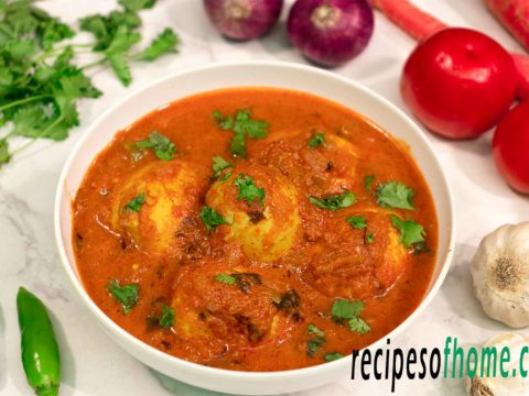 spicy egg curry recipe serve on white bowl,garnsih with freshly chopped coriander leaves