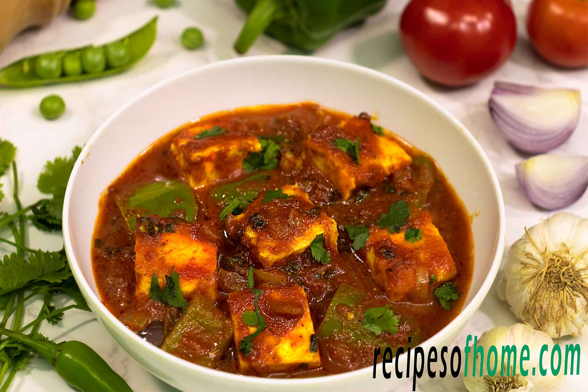 kadai paneer recipe serve in white bowl garnish with fresh coriander leaves