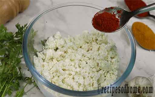sprinkle red chilli powder with scrambled paneer